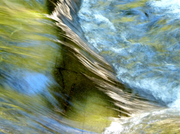 Green water running over rocks