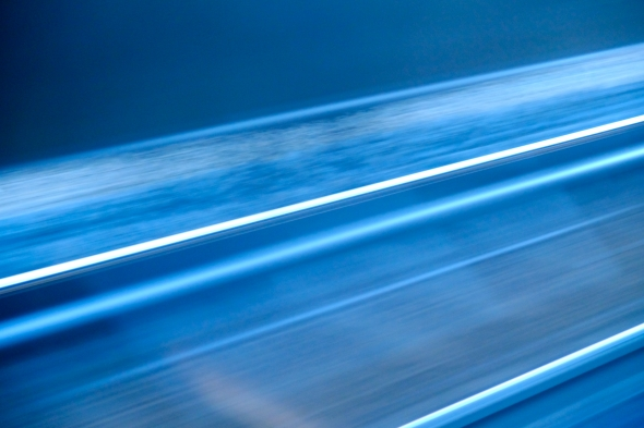 Abstract view in blue of moving railroad tracks