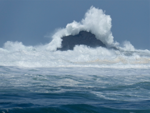 Large ocean wave breaking over coastal rocks