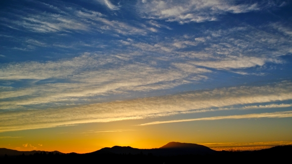 Sunset sky with mountains silhouetted in distance and high, white clouds against blue and yellow sky