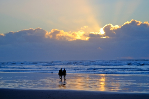 Silhouette of couple walking toward setting sun on an Oregon beach