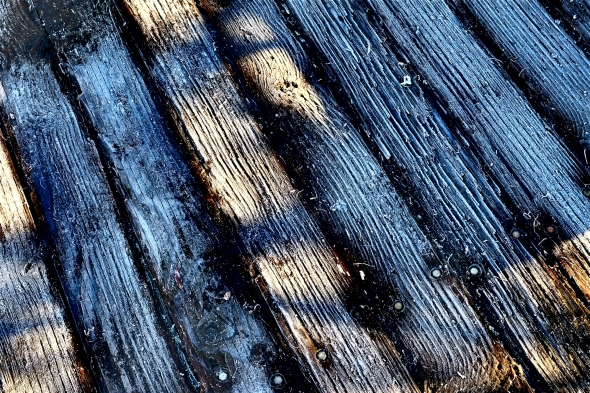 Detail of frost-covered wooden boardwalk in sun and shadow