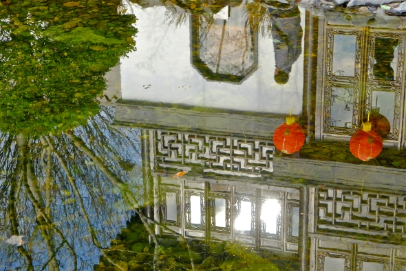 Reflection of teahouse, trees and passerby in garden pool