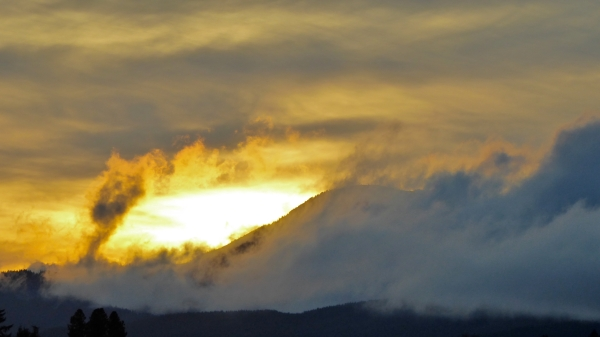 Sun setting in cloudy sky over mountain ridge wrapped in clouds
