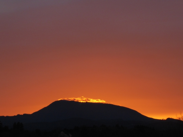 Low mountain silhouetted against orang sky after sunset