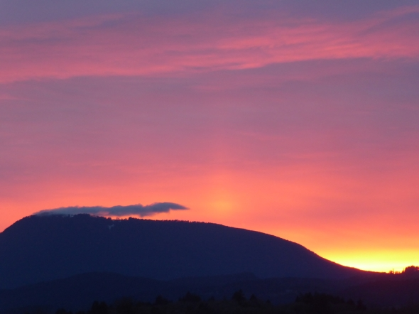 Pink and purple pastel sky above silhouetted mountain after sunset