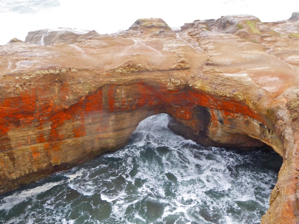 Tan and orange sea cliffs with foaming ocean surging through rocky archway