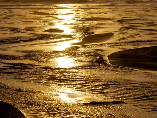 Sunlight reflected in shallow runnels on golden sandy beach