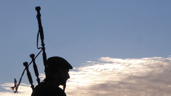 Silhouette of bagpiper with blue sky and glowing clouds in background