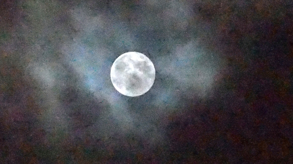 Full Moon partly shrouded by clouds in colorful dark sky