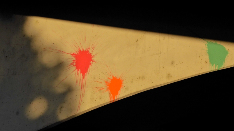 Red, orange and green paintball splashes on concrete overpass