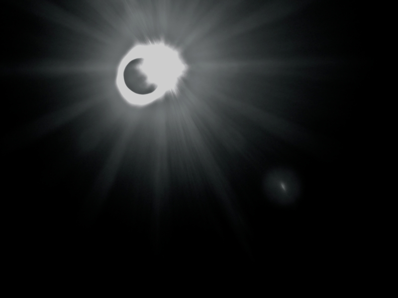 Total solar eclipse with bright flash at upper right