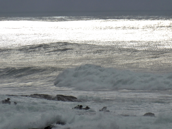 Ocean waves, offshore rocks and grey sky
