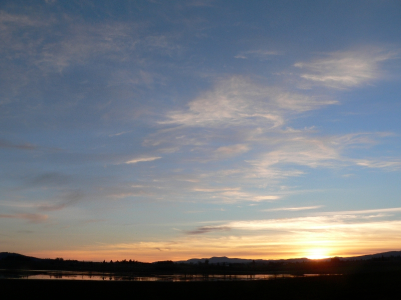 Sunset with bright clouds in sky over wetlands lansdcape