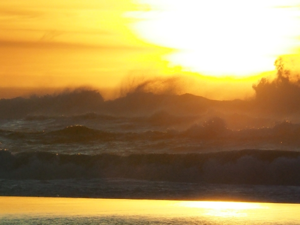 Dark Surf, Sun and Orange-Yellow Sky