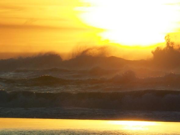 Dark Surf, Sun and Orange-Yellow Sky