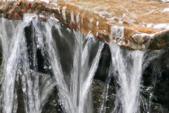 Water falling from small stone ledge