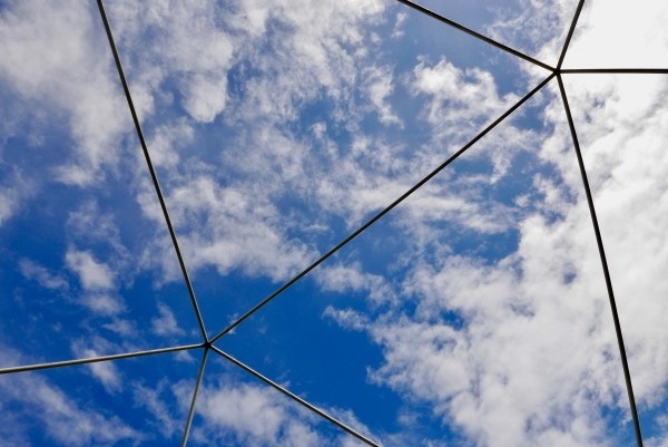 Blue sky and white clouds framed by triangular shapes