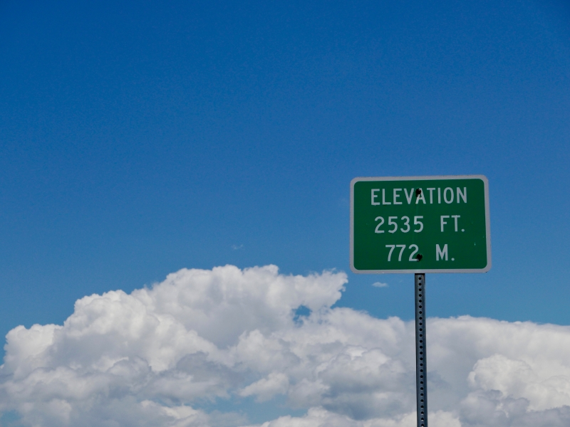 Elevation sign with blue sky and white puffy clouds