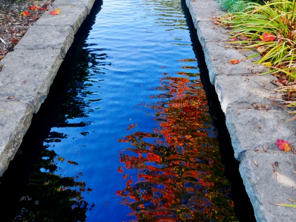 Small canal with orange leaves reflected in the water