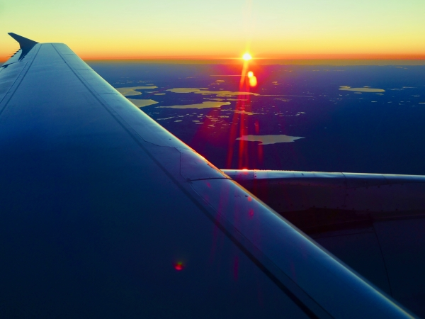 Airplane wing and setting sun over flat Florida landscape with many lakes