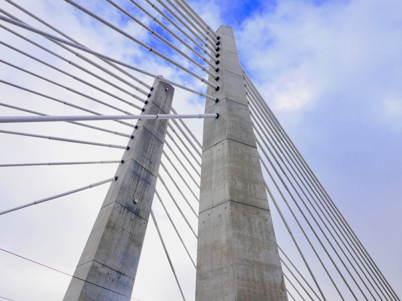 Two concrete columns and many parallel steel cables on bridge