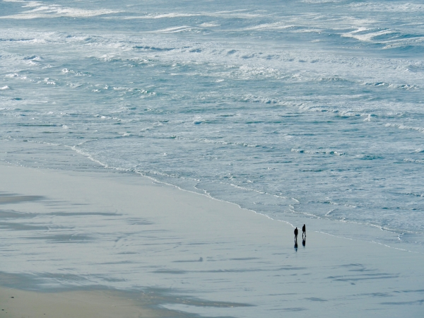 Two people walking next to blue ocean surf