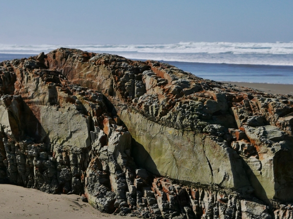 Rock outcrop on beach with surf
