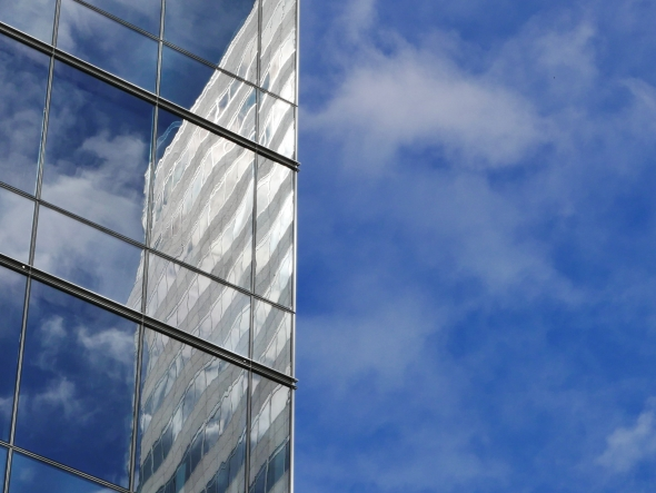 Blue sky and reflection of sky and skyscraper in another skyscraper