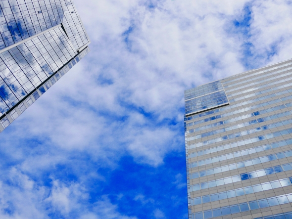 Two skyscrapers and blue sky with white clouds