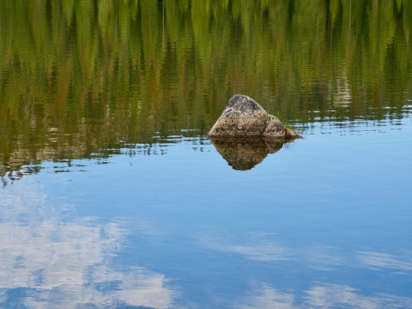 Rock in lake with reflections of trees and sky