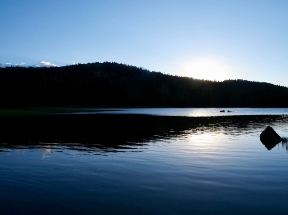 Blue lake and silhouetted hills at sunset