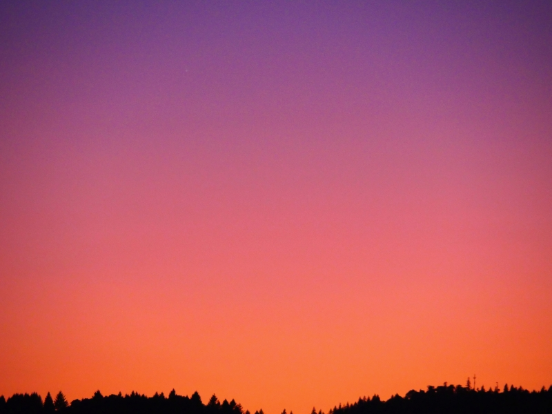 Glowing pastel sky over silhouetted horizon