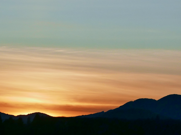Silhouetted mountains and orange sky