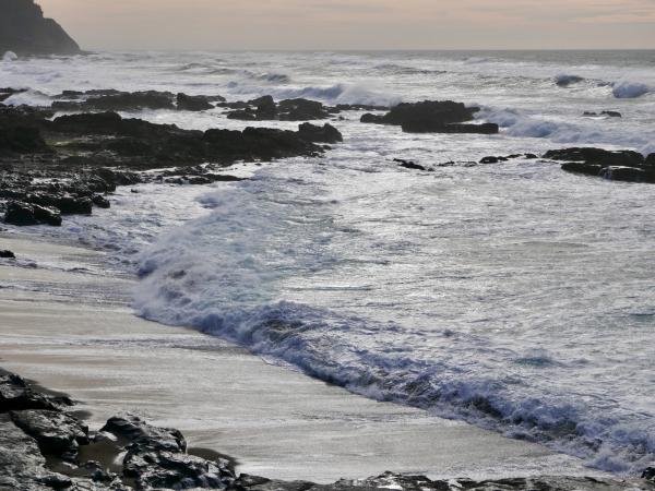Surf and dark rocks