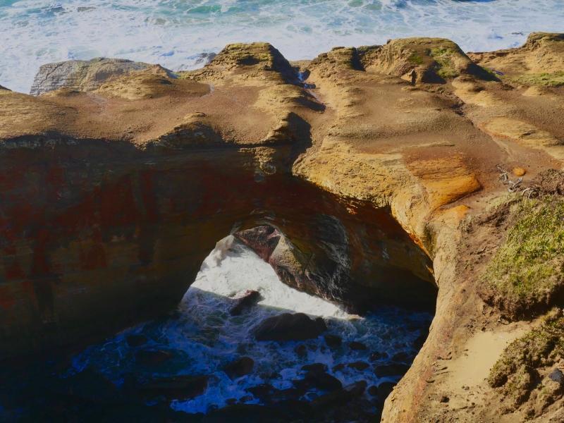 Ocean flowing through natural rock arch