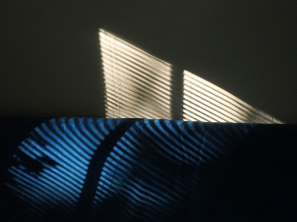 Shadows of blinds on futon and wall